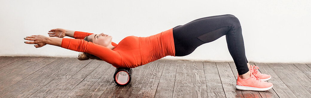 A woman using a foam roller.