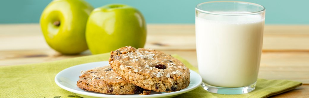 Apple breakfast cookies on a plate next to a glass of milk.
