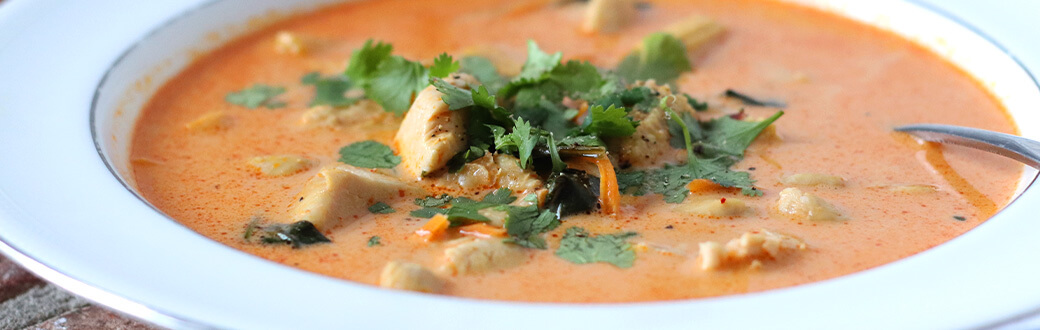 chicken coconut curry soup in a white bowl