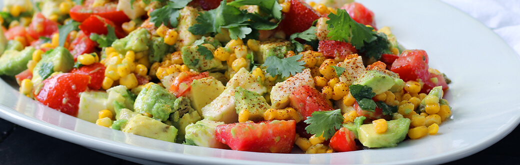 a plate of corn and avocado salad.