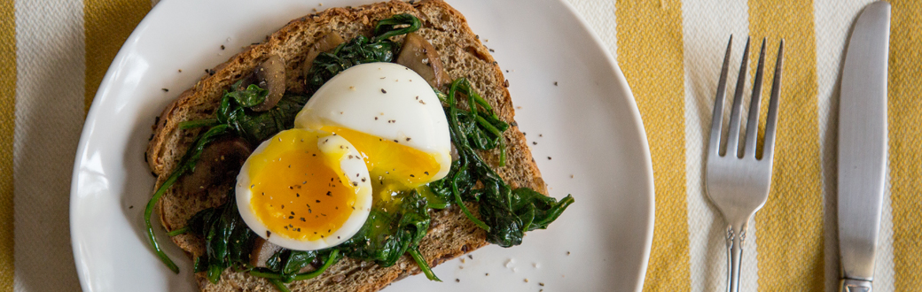 A halfed soft boiled egg on cooked spinach and toast.