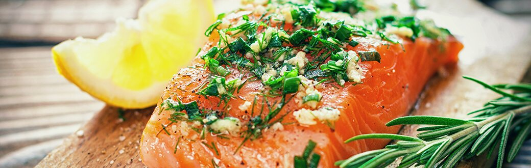 A salmon fillet topped with herbs.