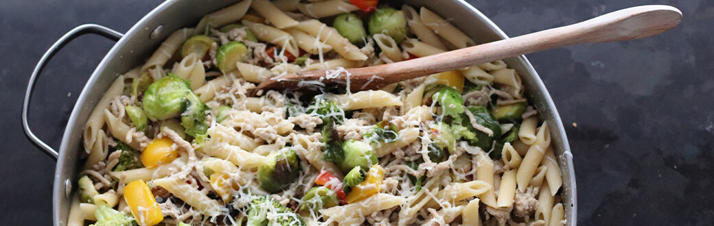 Pasta primavera topped with cheese.