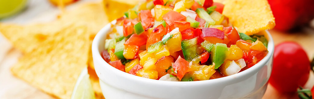 Fresh Peach Pico De Gallo in a bowl served with chips.