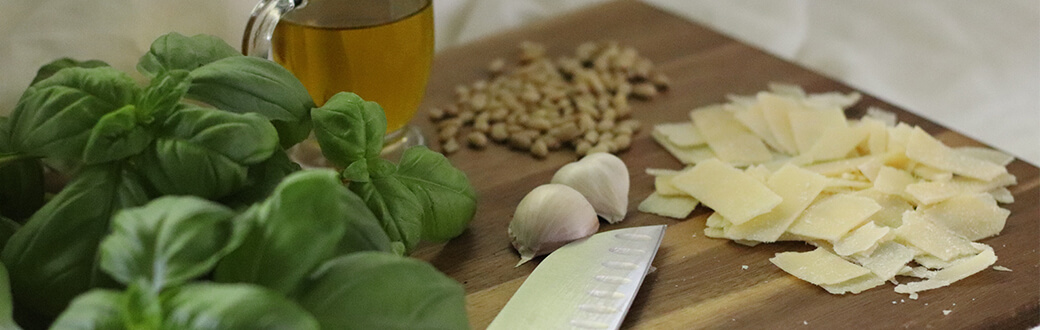 pesto ingredients on a wooden cutting board.