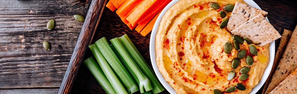 hummus in a bowl next to vegetables.