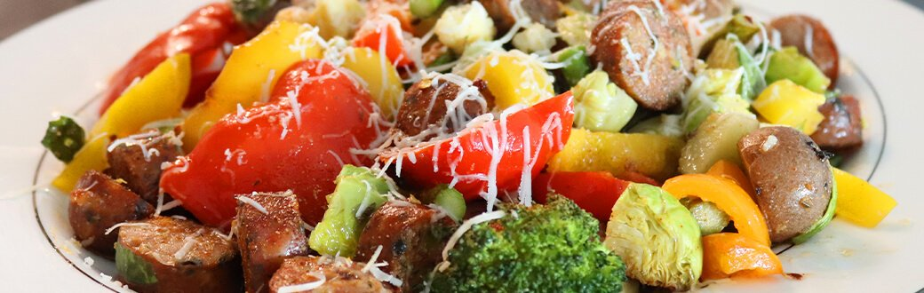 Roasted vegetables with sausage and Parmesan cheese on a plate.