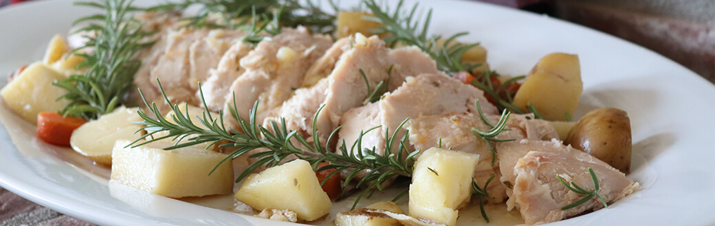 Sliced turkey, potatoes, and carrots on a plate with rosemary sprigs.