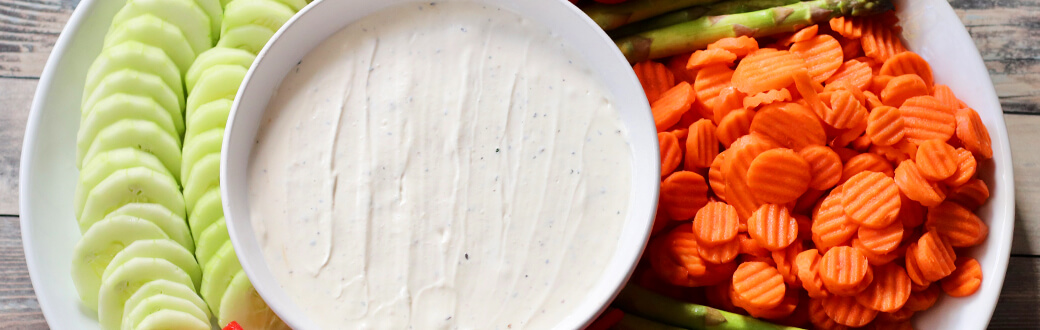 Cut veggies next to a bowl of white truffle dip.