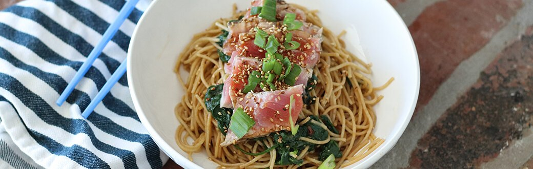 Seared tuna with spinach and whole wheat noodles in a white bowl.
