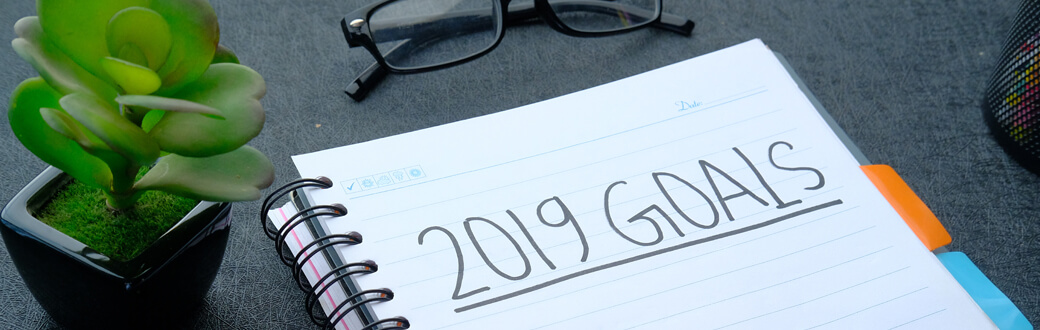 "A pad of paper on a table with ""2019 Goals"" written on it."