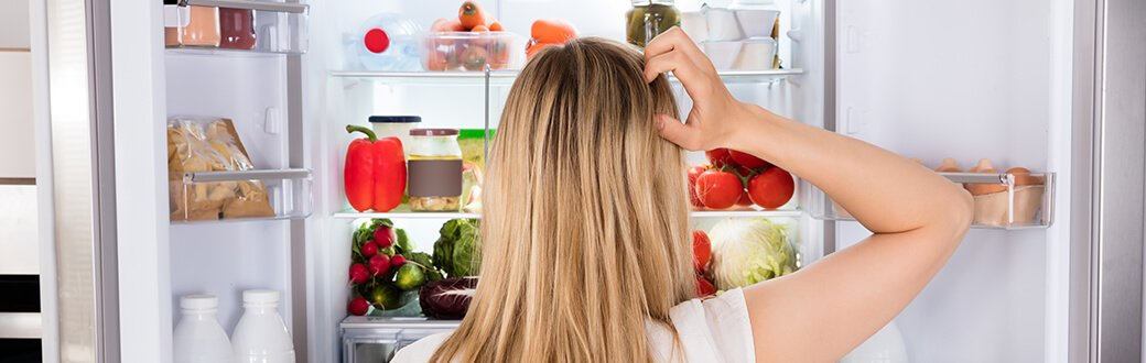 A woman scratching her head in front of an open refrigerator.