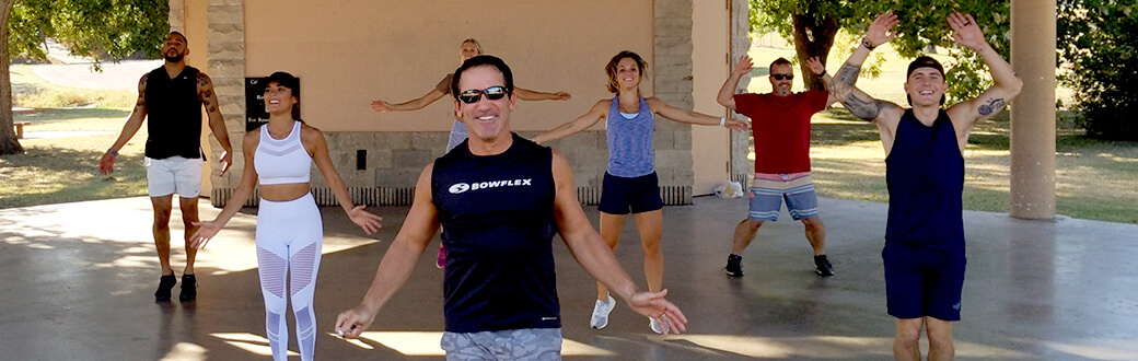 Smiling people doing jumping jacks