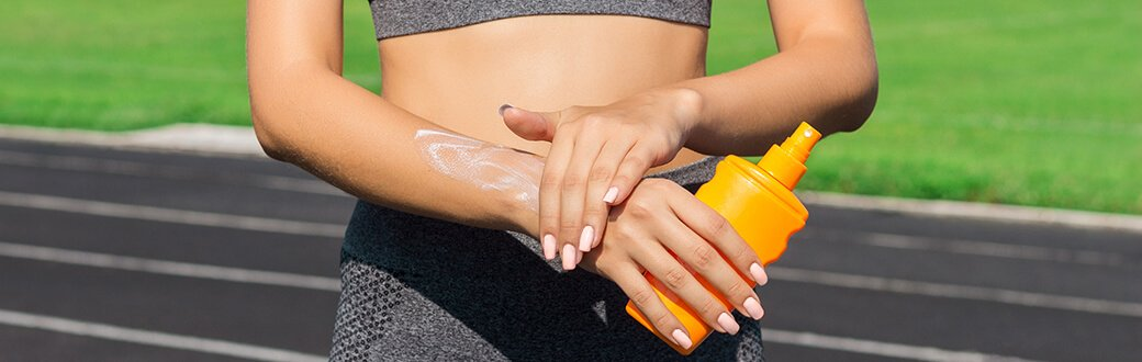 A fit woman applying sunscreen on her wrist.