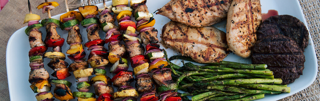 Barbecued foods including asparagus, hamburger patties, chicken and kebab skewers
