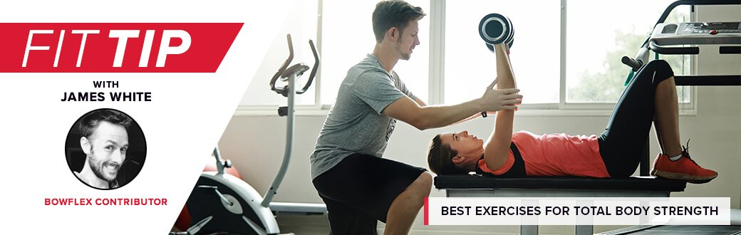 A trainer helping a person with a bench press.