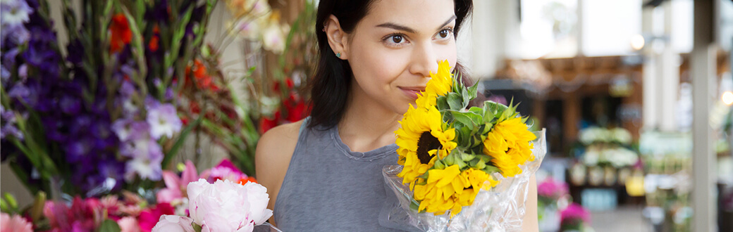 A woman smelling a bouquet of sunflowers.