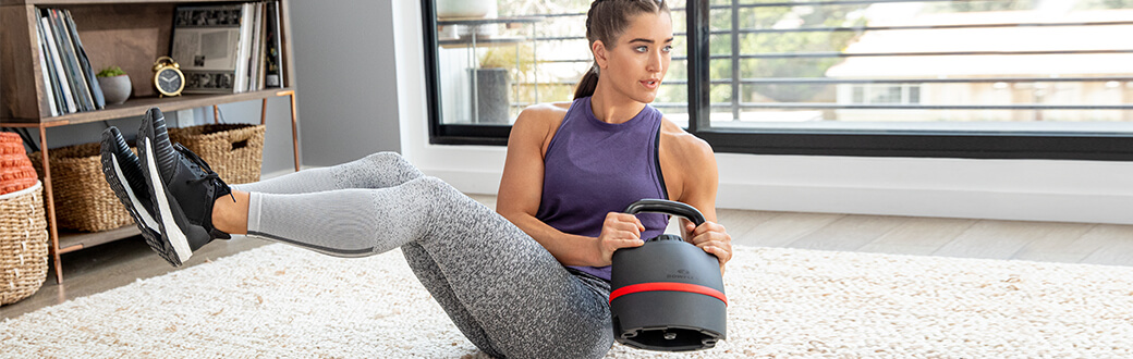 A woman working out with a Bowflex 840 Kettlebell.