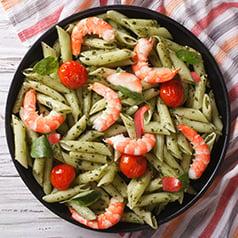 Close up of a bowl of pesto shrimp pasta