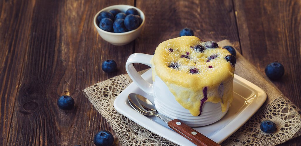 A mug muffin with blueberries.