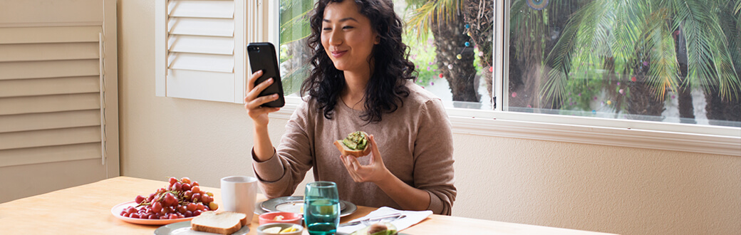 A woman using her phone while eating.