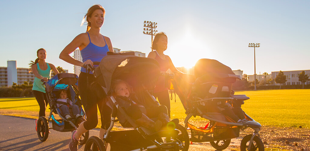 3 women running outside while pushing strollers.