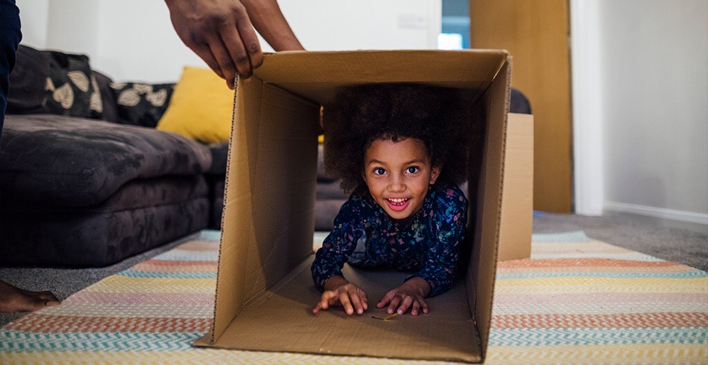 Child climbing through a cardboard box