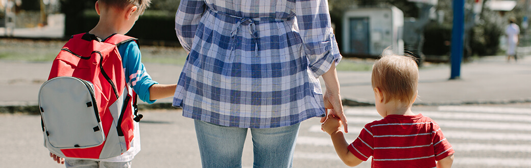 A woman holding hands with two childern while crossing a street at a crosswalk.