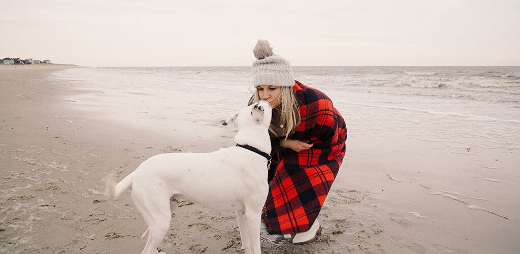 A woman on the beach with her dog