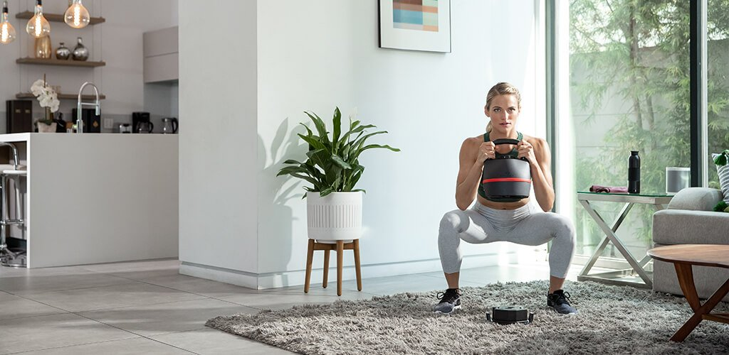 A woman performing a squat with an 840 adjustable kettlebell.