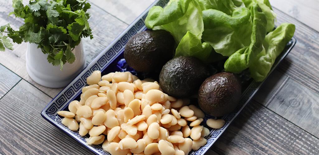 Cilantro, white beans, avocado, and lettuce on a counter.
