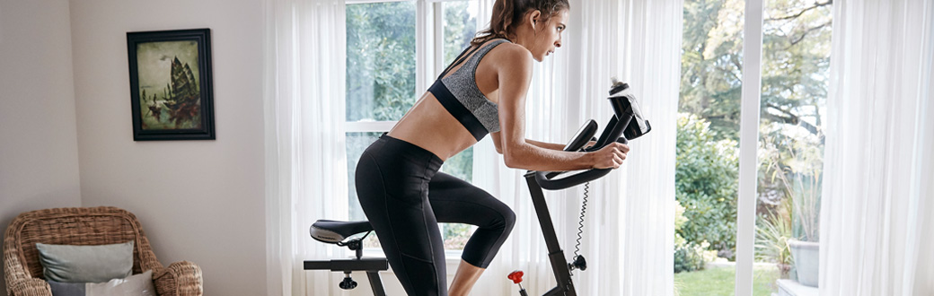 A fit woman working out on a Schwinn IC2 bike.