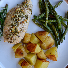 A plate of roasted chicken, green beans, and potatoes.