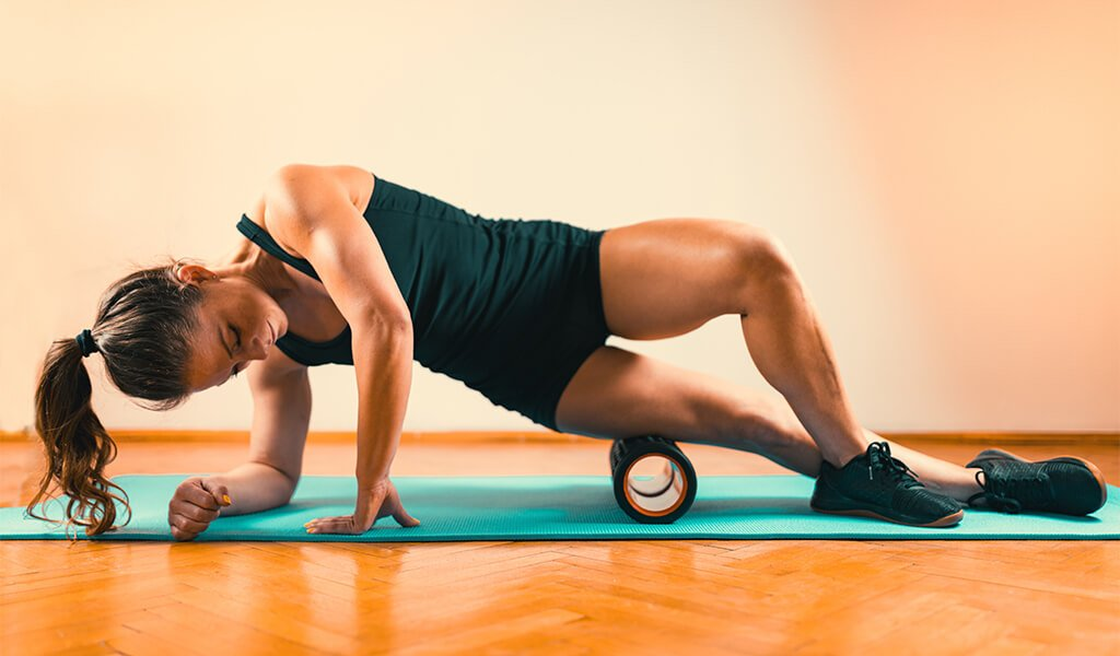 a woman using a muscle roller on her quadriceps