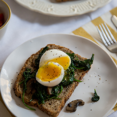 Close up image of a soft boiled egg on top of cooked spinach on toast.