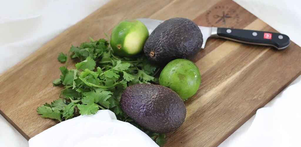 avocado, lime, and cilantro on a cutting board