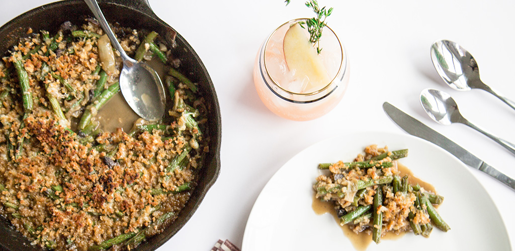 Green beans and caramelized onions in a skillet and on a plate next to a tasty looking drink.