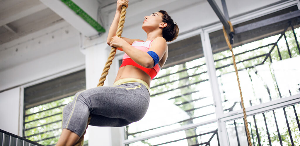 A woman using the j-hook technique to climb a rope.
