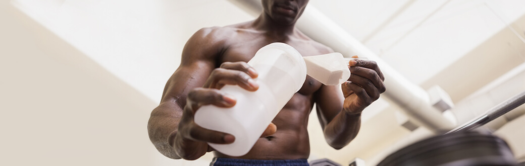 A man scooping protein powder into a bottle.