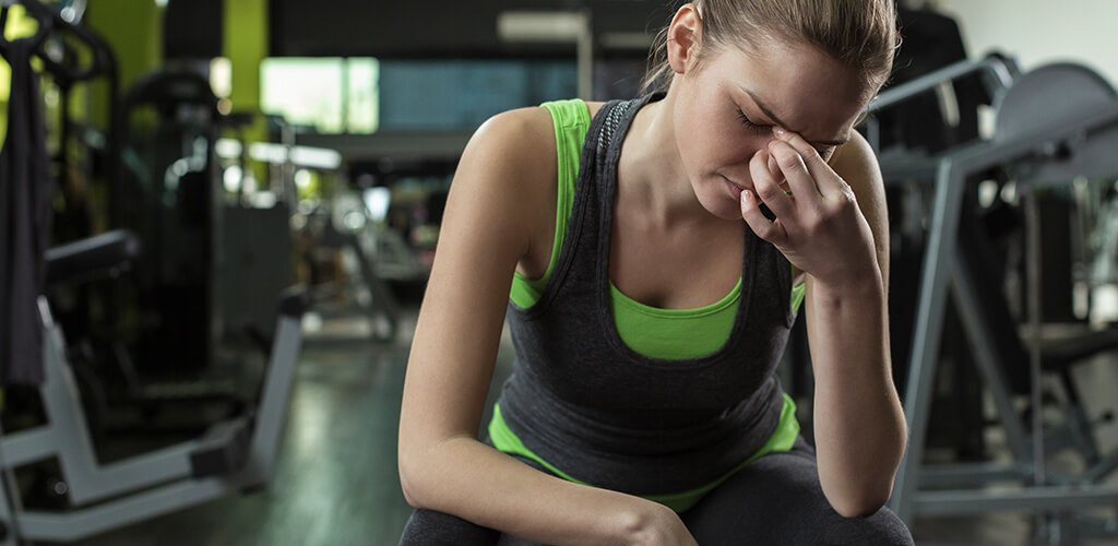 A woman in a gym looking stressed.