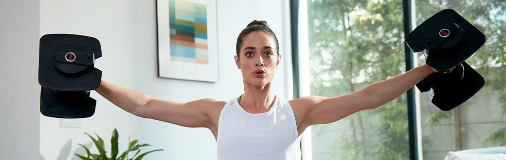 A fit woman holding dumbbells out to her sides.