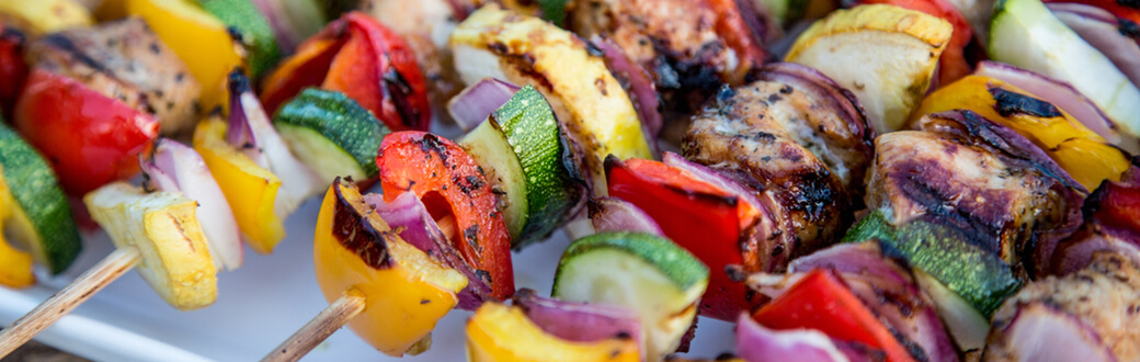 Grilled chicken and veggie kabobs on a plate.
