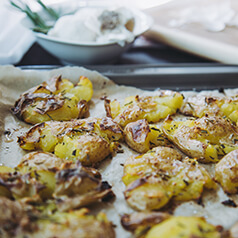 Cooked smashed potatoes on parchment.