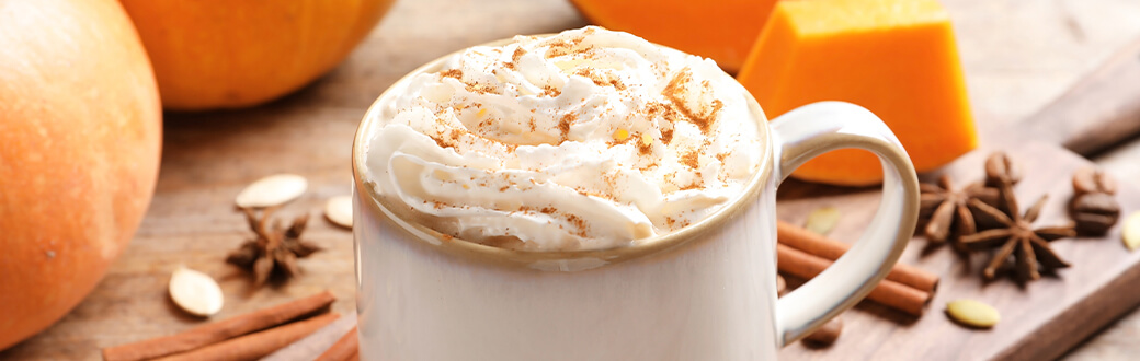 A pumpkin spice latte with whipped cream on a wooden table.