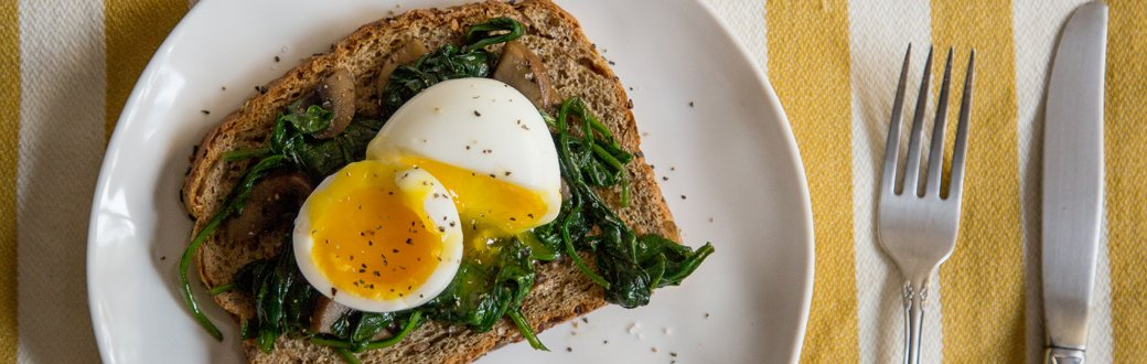 Soft boiled egg on cooked spinach and toast.