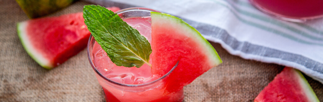 a small glass of watermelon mojito mocktail with mint and watermelon garnish.