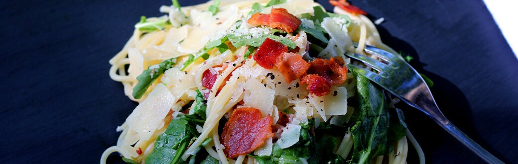bacon arugula pasta on a plate.