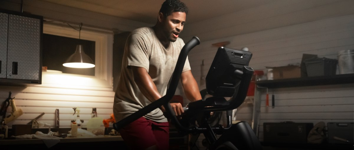 A man using a Max Trainer compact elliptical in his cramped garage.