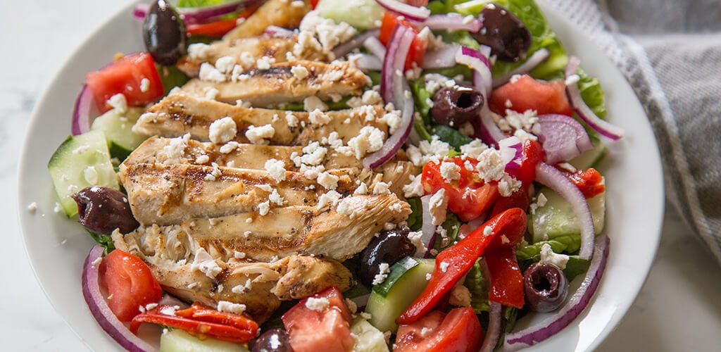 Greek marinated chicken over a greek salad on a table.