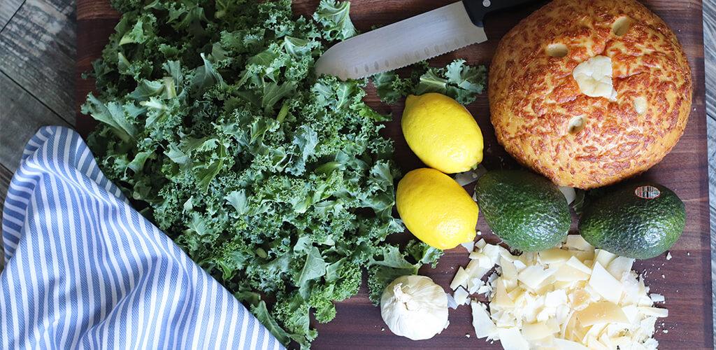 kale, lemon, avocado, garlic, grated cheese on a cutting board.